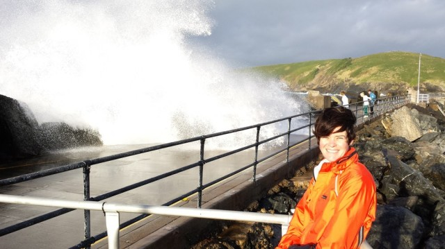 Jen on the breakwater with waves breaking